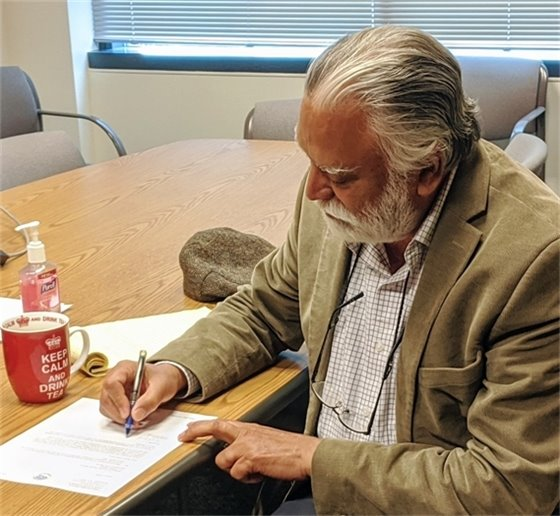 County Executive Satpal Sidhu signs Whatcom County's application for Phase 2.