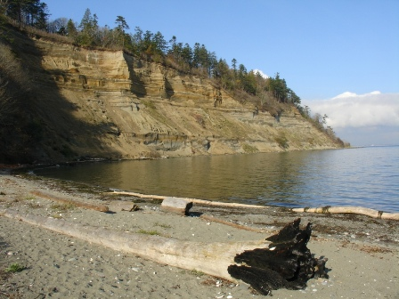 The beach line at Lily Beach with the mountain side surrounding the cove