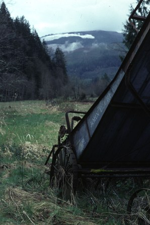 Old Farm equipment in a farm meadow among the mountains